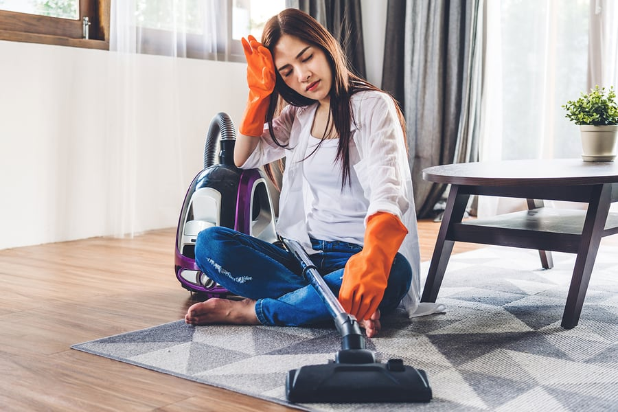young woman sitting on floor with vacuum